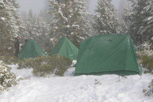 Winter campsite showing prepared campers in snow.