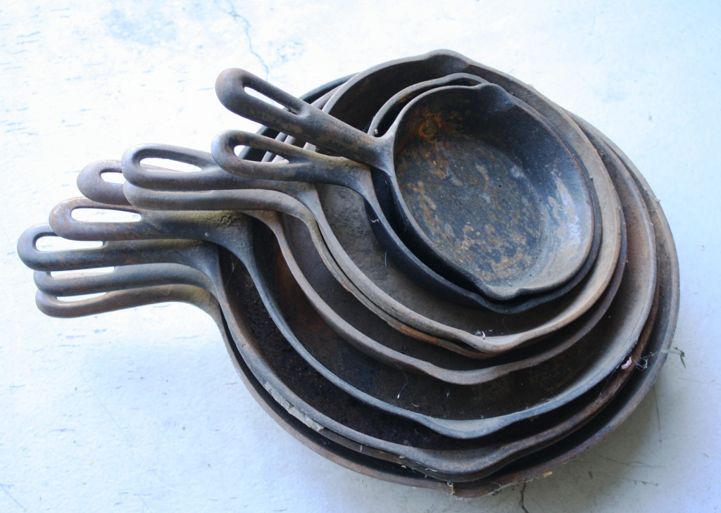 This stack of garage sale cast iron skillets can be restored to usefulness with a little work.