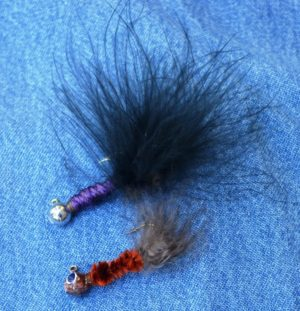 These leadhead jig lures were improvised from available materials. The body in both are composed of wool yarn. The tail on the top lure is made of a marabou feather, and the bottom tail is part of a pheasant feather. Both these patterns are proven and effective.