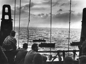 U.S. Marines wait aboard a Coast Guard manned combat transport at Tarawa for the invasion barges that will take them ashore. Beyond the rail Coast Guard coxswains can be seen