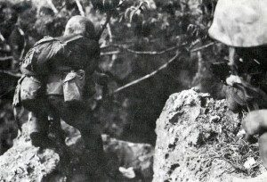 A Marine advances on a cave on Saipan (National Archives, Marine Corps)