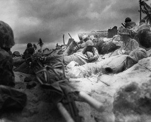Marines seek cover amongst the dead and wounded behind the sea wall on Red Beach 3, Tarawa. (National Archives, Marine Corps)