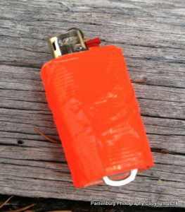 Add several feet of duct tape and a poptop to a standard BIC mini lighter and you have a firestarting kit. Secure the lighter to a lanyard with the poptop.