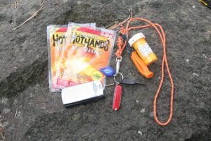 These items are lightweight, easily-carried and could save your life if you're injured while running. From left: handwarmers, cell phone, flashlight, Swiss Army Classic knife, Boy Scout flint stick, whistle, and firestarter.