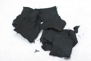 "The denim material is ""cooked"" in an airtight container until it is black. Then it will catch a spark."