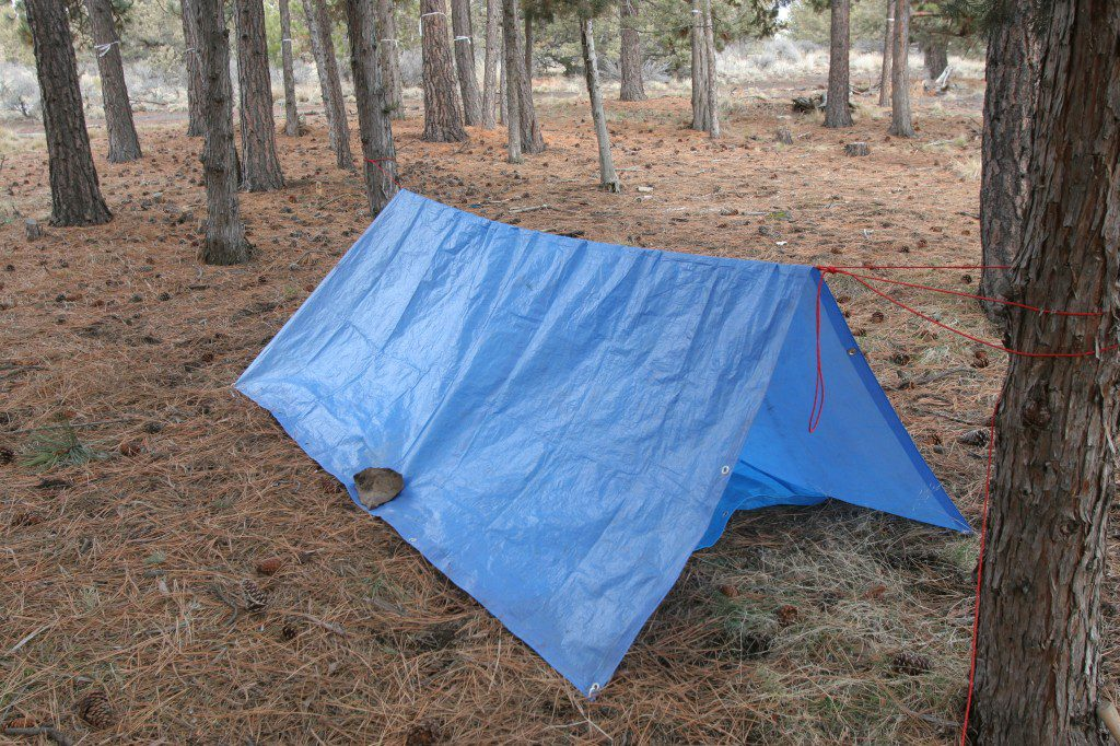 Tie down a tarp to make an emergency shelter secure, safe